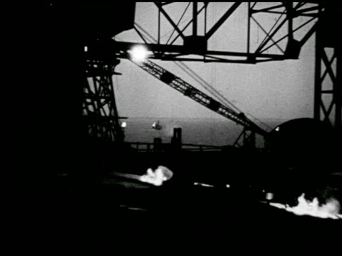 stockvideo's en b-roll-footage met partially completed ship beyond railroad bridge night vs people welding on ship deck vs man operating automated hammer on large heated metal piling... - 1943