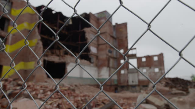Partially demolished abondoned warehouse with chain link fence around it -- pan to building through links in fence