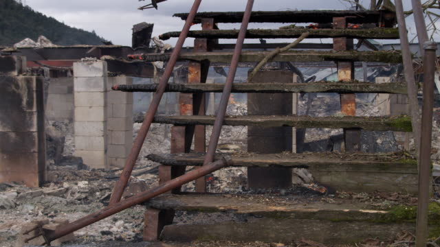 Partially destroyed stairs and burning rubble  in the remains of a house destroyed by fire