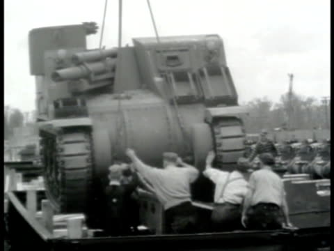 stockvideo's en b-roll-footage met partially disassembled tank being loaded onto train flatcar by crane workers securing tarp covered tank making wooden brackets to secure on railroad... - 1943
