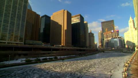 partially frozen, icy chicago river, partial metropolitan area city buildings & traffic across river bg, michigan avenue bridge distant bg .... - ミシガン橋点の映像素材/bロール