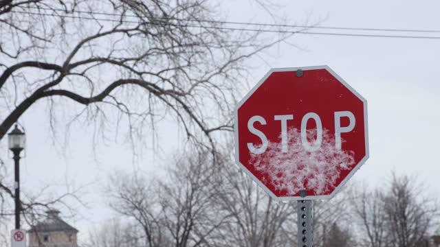vídeos y material grabado en eventos de stock de parcialmente cubierta de nieve señal de parada en un día tormentoso de diciembre - señal de stop