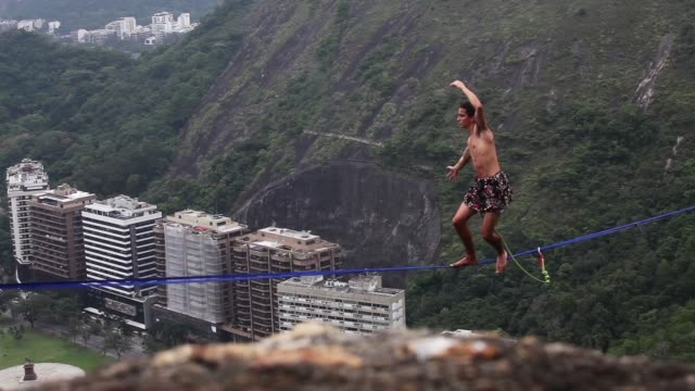 a participant balances during the highgirls brasil slack line event on november 2 105 in rio de janeiro brazil - participant stock videos and b-roll footage