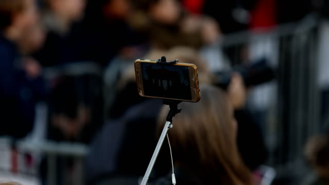 participant films the event with his smart phone with a pole, the brandenburg gate can be seen on the screen during the pre-program of the event.... - participant stock videos & royalty-free footage