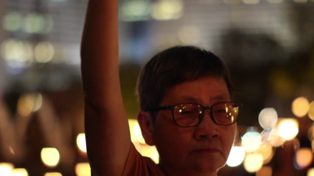 a participant holds a candle as she and others attend a candlelight vigil at hong kong's victoria park on june 4 to mark the 28th anniversary of the... - participant stock videos and b-roll footage