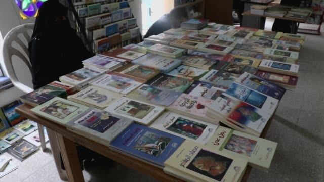 a participant in a book exhibition sits by her variety of books waiting for customers amid lack of visitors on september 23 2020 in sana'a yemen the... - participant stock videos & royalty-free footage