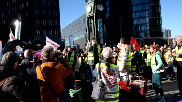 "participant speaks at the rally. supporters of the new left-wing ""stand up"" movement gather at a demonstration at potsdamer platz on february 16,... - participant stock videos & royalty-free footage"