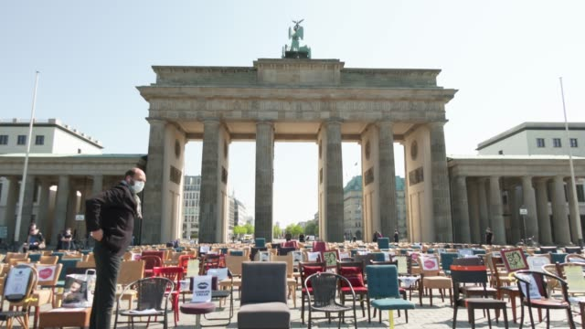 participant wearing a protective face mask attaches signs to restaurant chairs arranged in front of the brandenburg gate during a nationwide protest... - participant stock videos & royalty-free footage