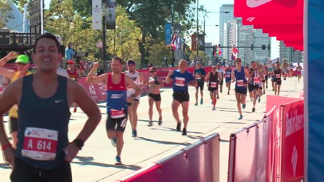 participants crossing finish line in the 2017 chicago marathon on oct. 8, 2017. - ランニングショートパンツ点の映像素材/bロール