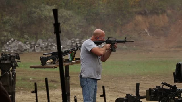 Participants fire beltfed machine guns during the Fall 2015 Knob Creek Machine Gun Shoot at Knob Creek Gun Range in West Point Kentucky US on Friday...