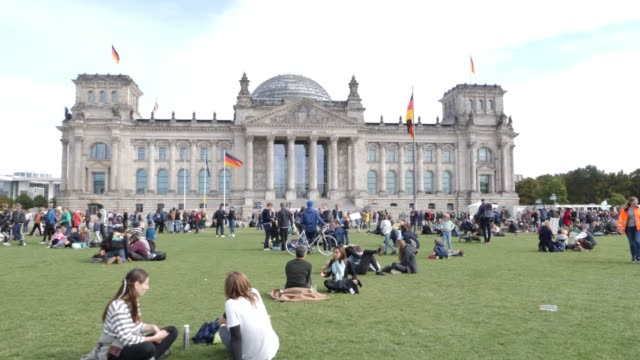 participants in the fridays for future movement protest and rest on the meadow of the reichstag during a nationwide climate change action day on... - german flag stock videos & royalty-free footage