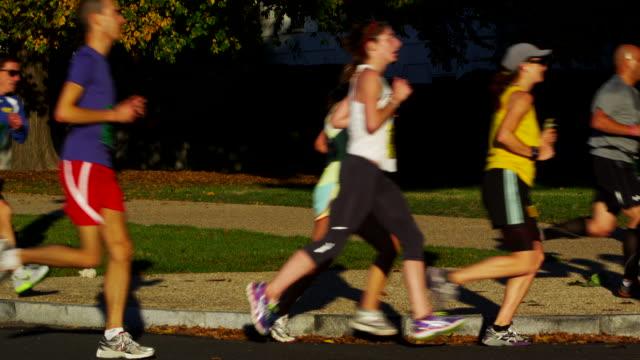 vídeos y material grabado en eventos de stock de participants in the u.s. army marathon run on a neighborhood street. - paso largo