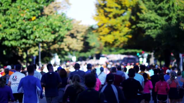 vídeos y material grabado en eventos de stock de participants in the u.s. army marathon run on a tree lined street. - paso largo