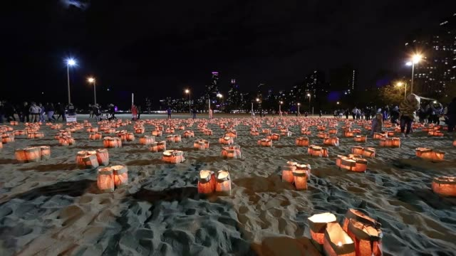 Participants light thousands of luminaries on North Avenue Beach during the annual 'Light Up the Lakefront' event to raise awareness for domestic...