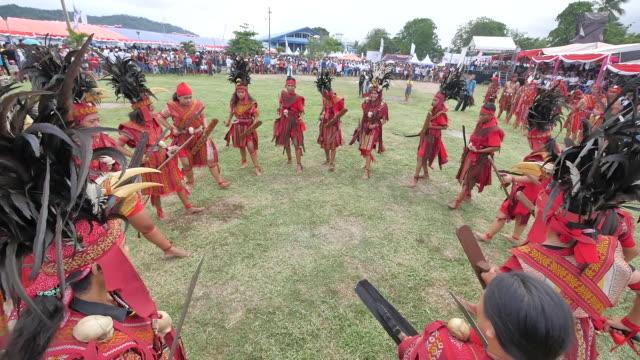 vídeos de stock e filmes b-roll de participants of the bitung festival wear the traditional maluku clothing they dance the war dance and enliven the event - dança da guerra