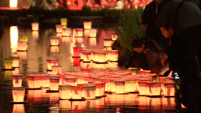 participants release floating paper lanterns onto a river in saga city, japan. - lantern stock videos & royalty-free footage