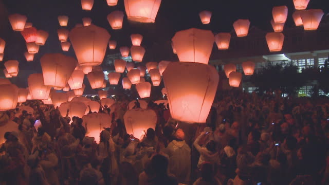 Participants release glowing paper lanterns into the sky during a festival in Taipei, Taiwan.