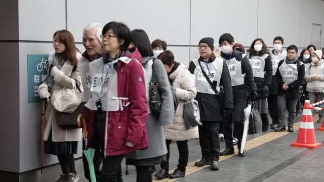 Participants stand outside a subway entrance before the start of a missileattack drill in Tokyo Japan on Monday Jan 22 Participants walk towards a...