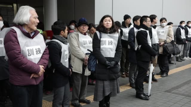 participants stand outside a subway entrance during a missileattack drill in tokyo japan on monday jan 22 participants walk towards a subway entrance... - ドリル点の映像素材/bロール