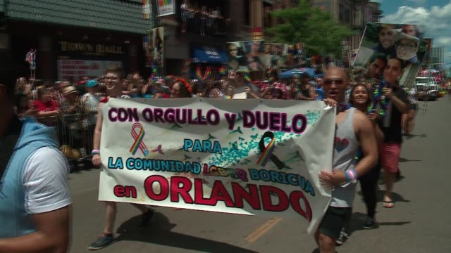 wgn participants walk in honor of orlando pulse nightclub shooting victims at the 48th annual chicago pride parade on june 25 2017 - 犯罪点の映像素材/bロール