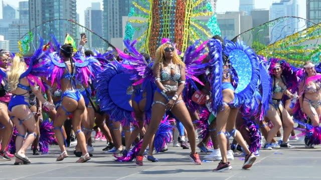 participants wearing multi-colored costumes parade in the city streets. 4x slow motion. the caribana, also known as the toronto caribbean carnival,... - caribbean stock videos & royalty-free footage