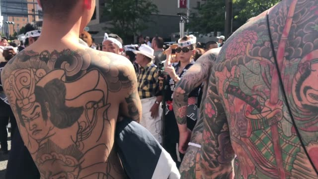 vidéos et rushes de participants with traditional festival outfit parade down the street toward asakusa shrine in the compound of sensoji temple during tokyo's one of... - tatouage