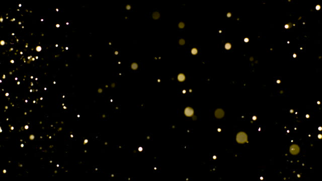 Particle gold glitter orbs twinkle on black background, bokeh