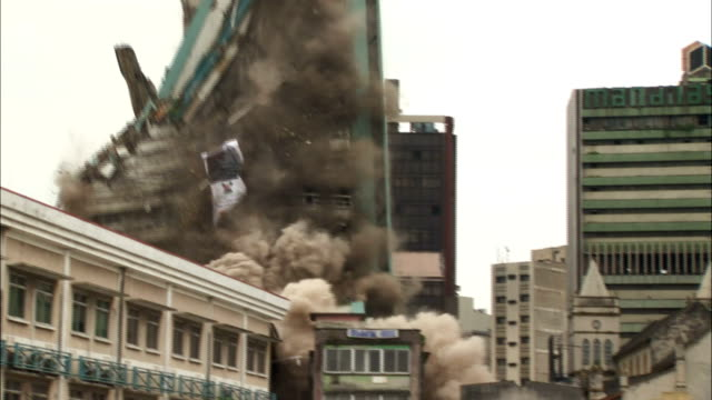vidéos et rushes de ws zi pan  partilly collapsed nidb building in middle of  city is demolished in  controlled implosion using explosives collapses and creates huge cloud of dust / lagos, lagos state, nigeria - imploding