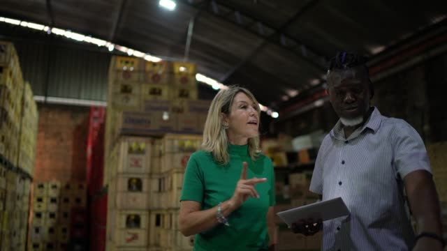 partners / coworkers walking and using digital tablet at warehouse - leadership stock videos & royalty-free footage
