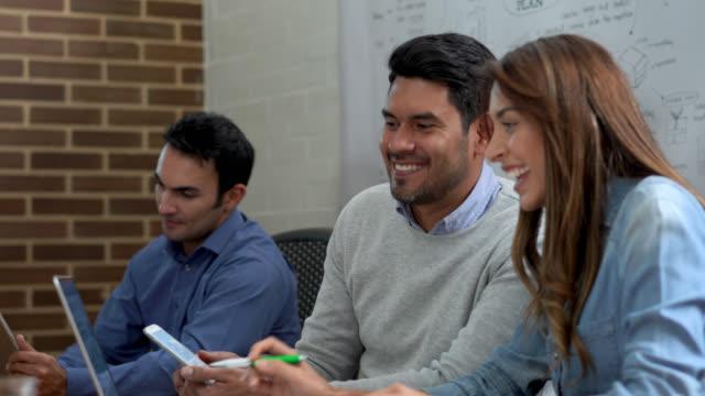 vidéos et rushes de partenaires lors d'une réunion, parler en regardant l'écran d'un smartphone et un ordinateur portable, les deux très heureux à la recherche - vêtements décontractés