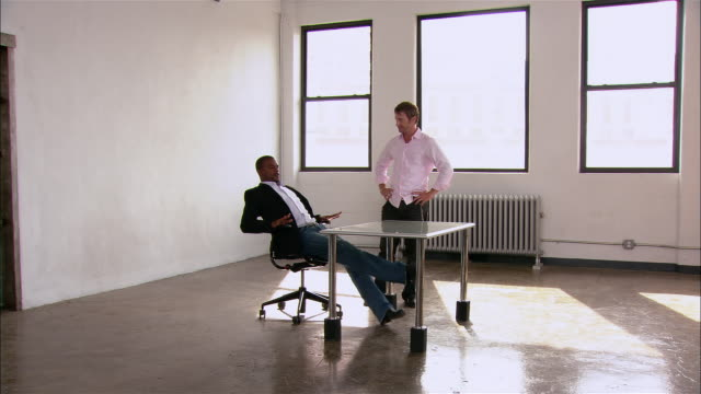 vídeos de stock e filmes b-roll de partners in startup firm taking turns sitting down at first desk in empty loft space / new york city - sentar se