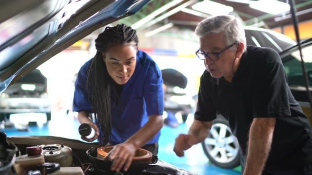 vídeos y material grabado en eventos de stock de mecánico de socios que trabaja en un taller de reparación de automóviles - mecánico de coches