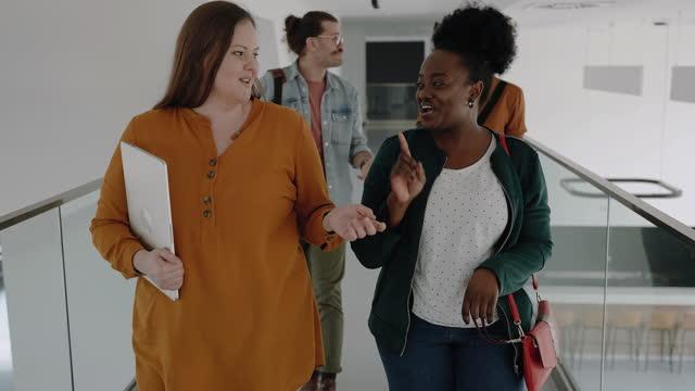 partners walking down corporate hallway - genderblend stock videos & royalty-free footage