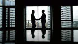 Partnership concept: two man silhouette handshake