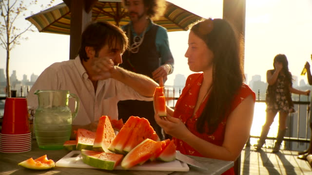 stockvideo's en b-roll-footage met ms party on balcony, couple eating watermelon  / brooklyn, new york - oceanische etniciteit