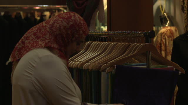 pashmina scarves. on a woman with a headscarf looking through pashmina scarves displayed on hangers in a shop. - shawl stock videos & royalty-free footage
