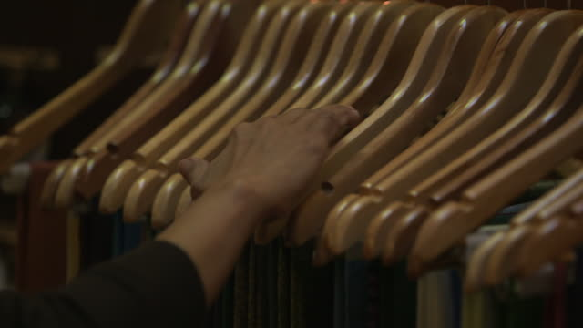 pashmina scarves. on a woman's hand as she looks through pashmina scarves displayed on hangers in a shop. - ハンガー点の映像素材/bロール
