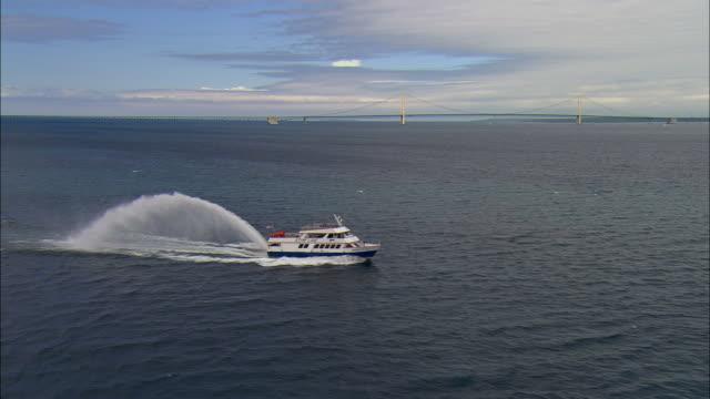 aerial pass around mackinac island ferryboat with bridge in background/ mackinaw city, michigan - 英字点の映像素材/bロール