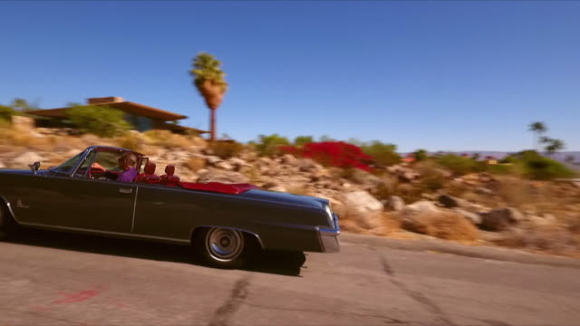 ts pass-by classic convertible american car driving up a hill and passing mid-century modern house on top of rocky hill - palm springs california stock videos & royalty-free footage