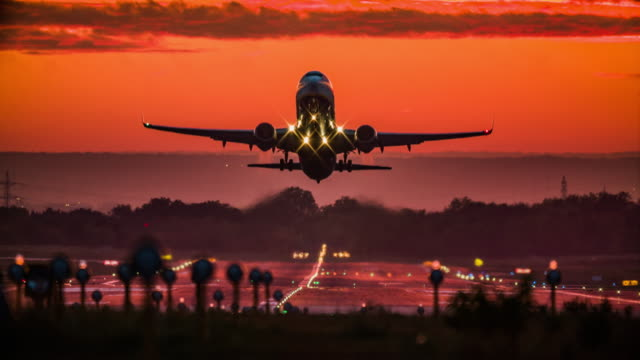 vídeos de stock e filmes b-roll de passenger airplane taking off at sunset - taking off