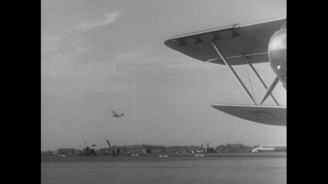 b/w passenger biplanes landing at airport / croydon, england, united kingdom - ロンドン クロイドン点の映像素材/bロール