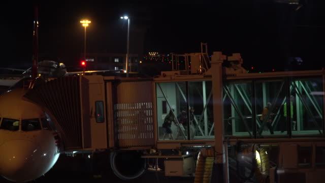 vídeos de stock, filmes e b-roll de embarque do passageiro do terminal do aeroporto ao avião na noite - embarcar