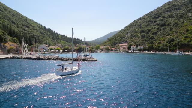 stockvideo's en b-roll-footage met passagiersboot naderen kleine haven in de egeïsche zee - griekenland