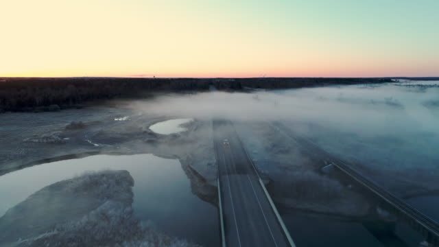 a passenger car appearing from the dense fog on a deserted highway in chippewa national forest, minnesota, in the early cold morning in spring. aerial drone video with the backward camera motion. - minnesota stock videos & royalty-free footage