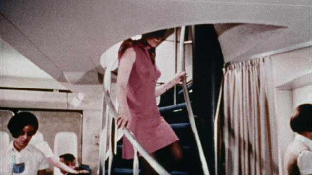 A passenger descends the stairs as flight attendants prepare snacks on a Boeing 747.