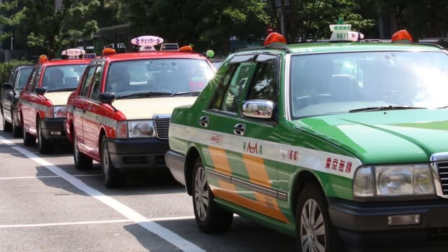 a passenger exits a taxi outside a train station in tokyo japan on monday july 11 taxis waits in line at a taxi stand outside a train station - taxi stand stock videos and b-roll footage