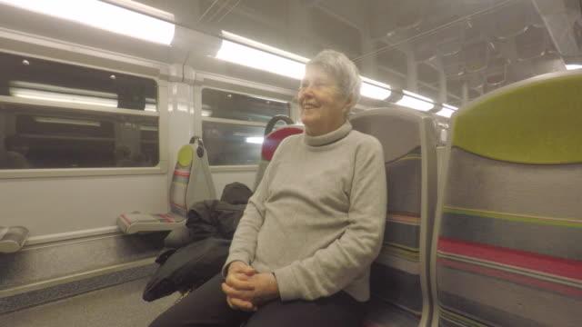 passenger in a suburban train, old person - interno di treno video stock e b–roll