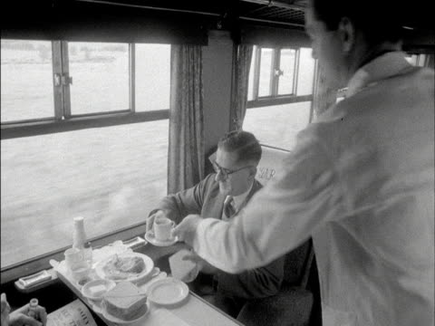 a passenger is served lunch in a restaurant carriage on board a passenger train 1960 - heißes getränk stock-videos und b-roll-filmmaterial
