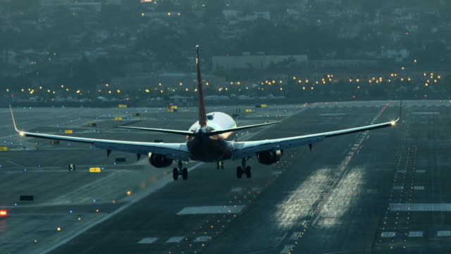 vídeos de stock, filmes e b-roll de ha pan ws of passenger jet airliner landing and touching down at dusk on airport runway lined with yellow glowing runway lights / san diego, california, usa  - aterrissando
