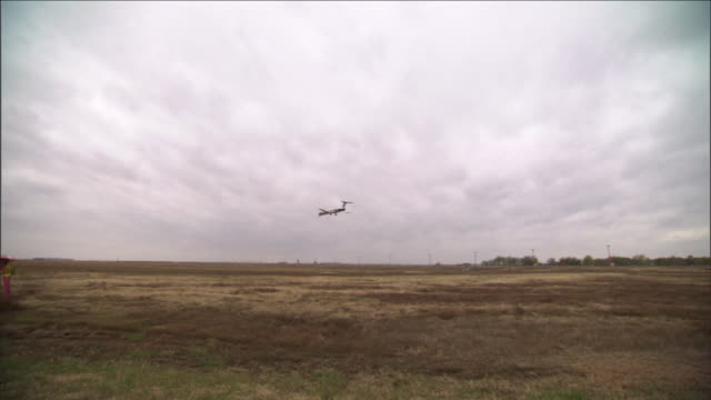 a passenger jet approaches a landing at dallas fort worth international airport on a cloudy day. - dallas fort worth airport stock videos & royalty-free footage